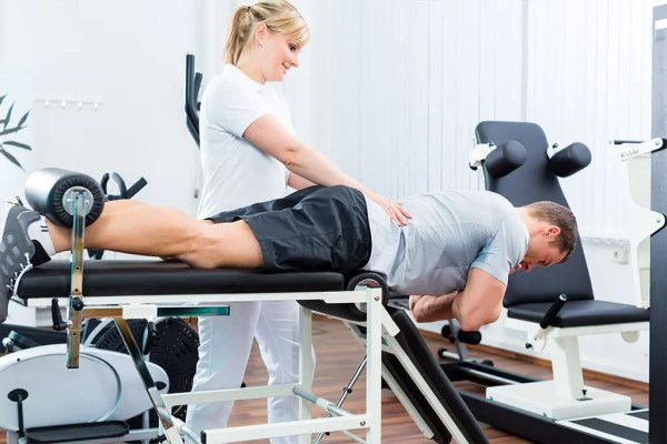 Image of a healthcare professional helping a patient perform exercises for low back pain and sciatica.