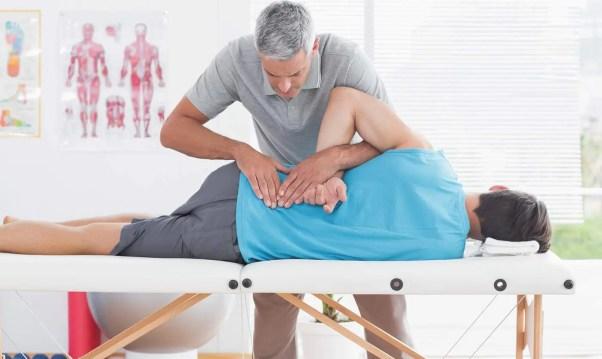 Immagine di un chiropratico che usa le regolazioni spinali per trattare un paziente per la lombalgia.
