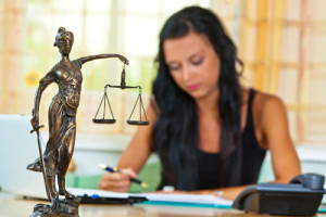 Scales of Justice Statue as female lawyer advocates against Tort Reform