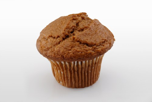 A single bran muffin with a muffin top.