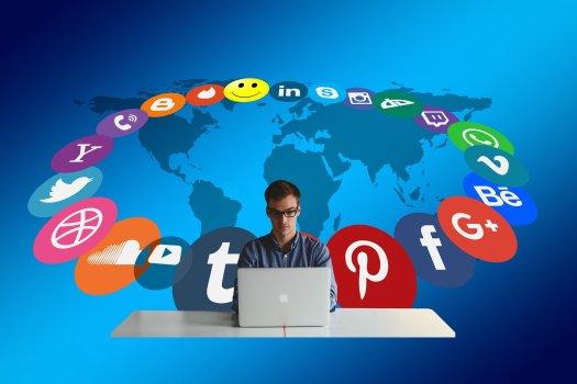 laki-laki di depan laptop deikelilingi logo-logo berbagai channel social media, seperti facebook, path, linked in, instagram dan lain-lain