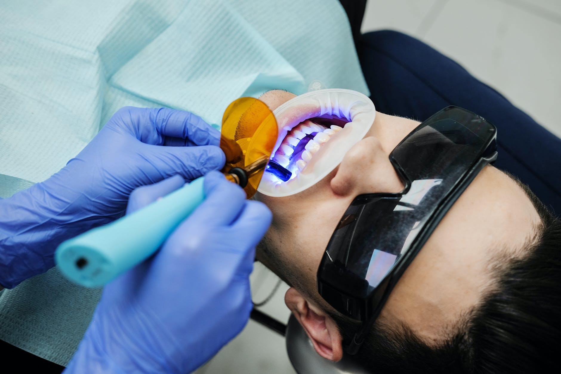 dentist making oral examine of patient with uv light equipment