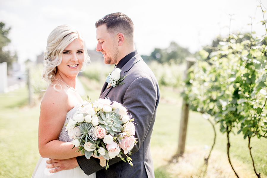 bride and groom give each other a hug at tomasello winery