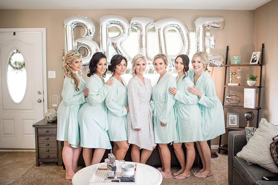 bridesmaids pose with the bride balloons