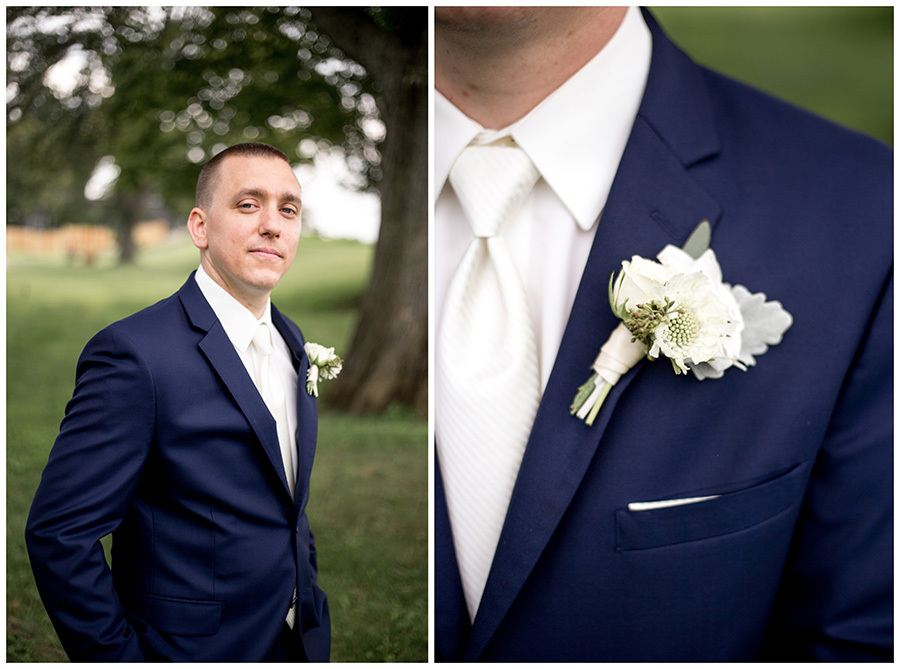 groom in a navy suit with a white flower