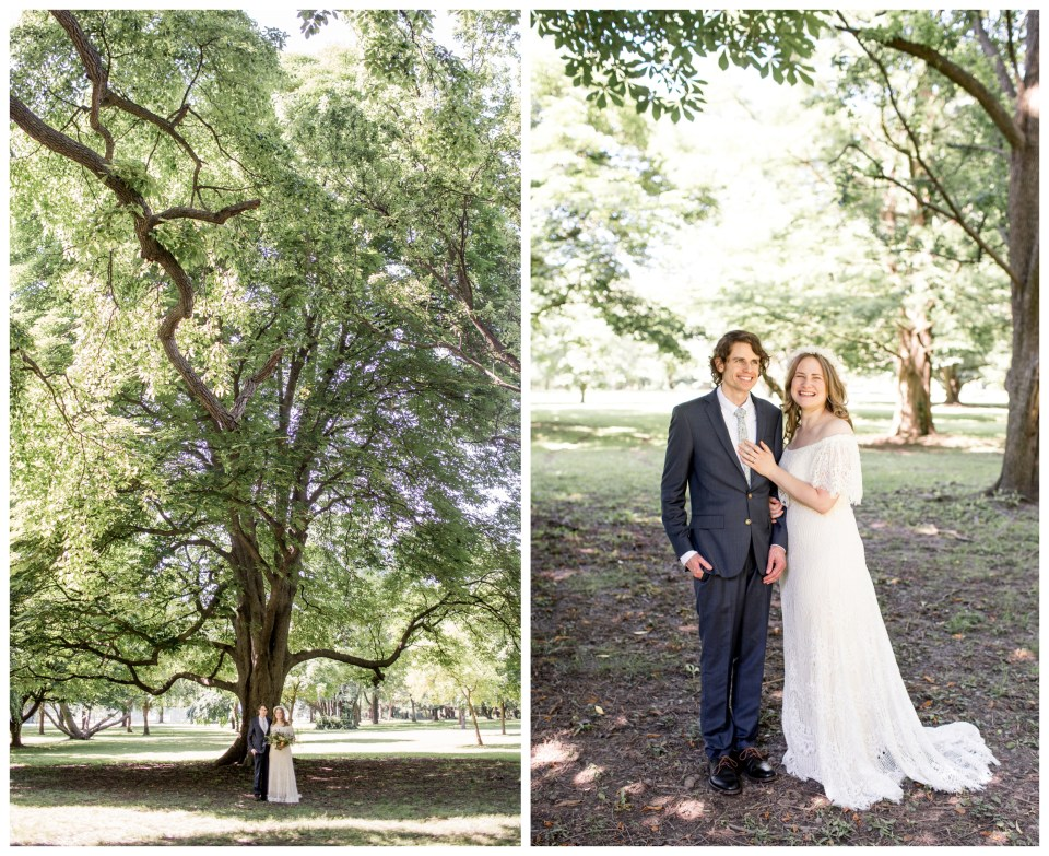 couple stands for wedding portraits beneath tall trees