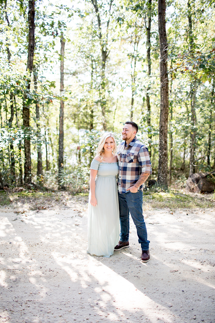 engaged couple takes a walk through the woods