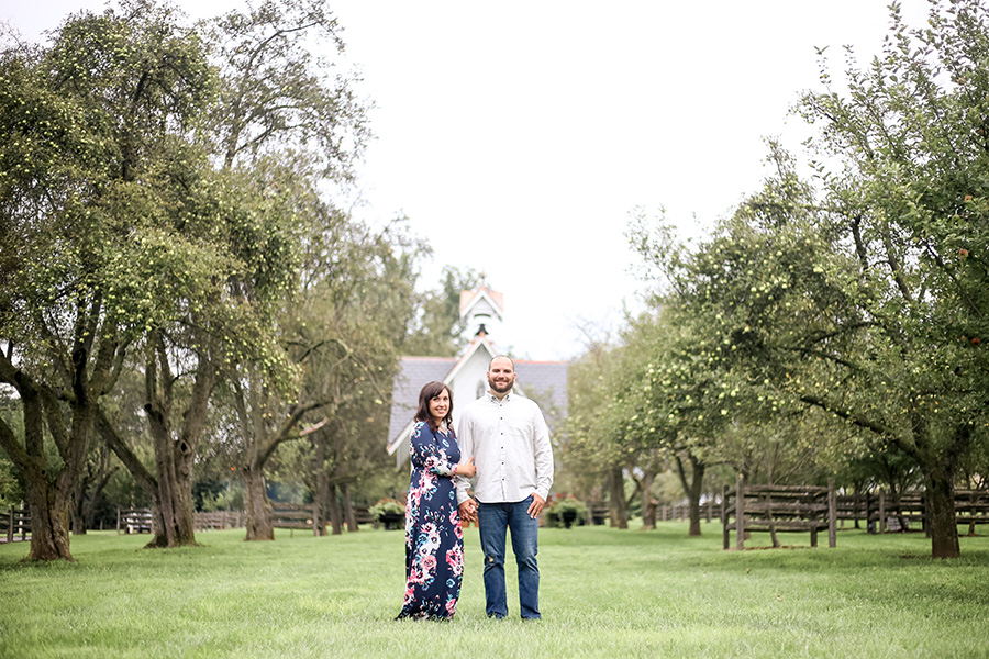 engaged couple at rustic venue in apple orchard