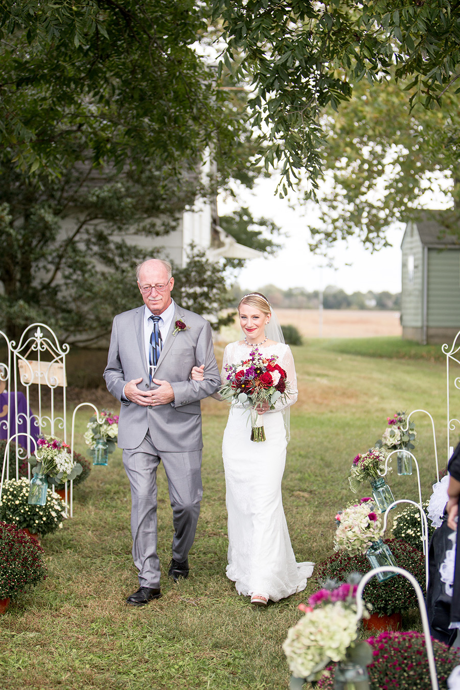 bride escorted down the aisle by her father at her farm ceremony