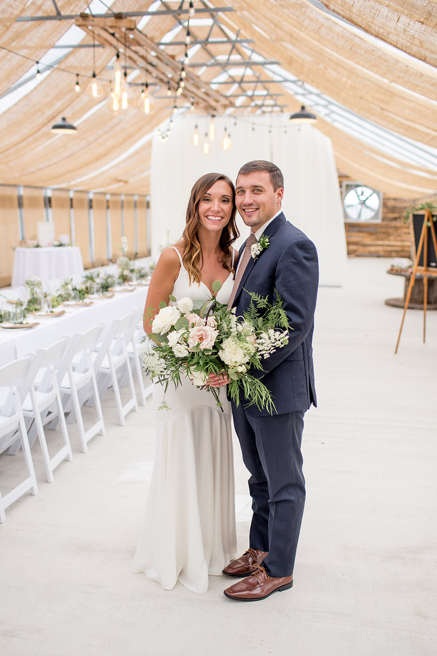married couple admires wedding decorations inside the greenhouse