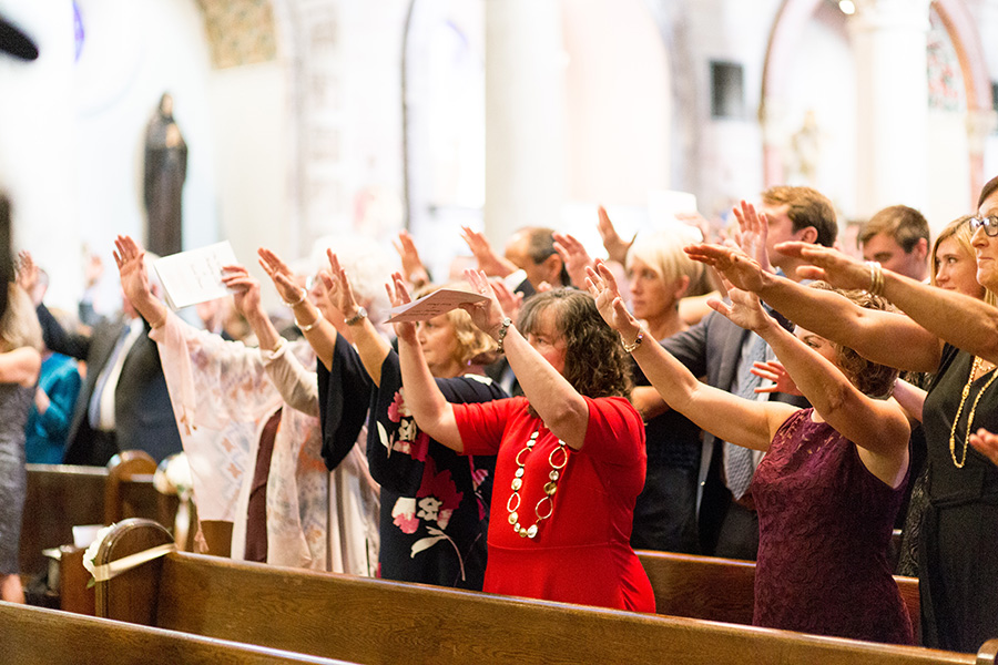 wedding guests show their support for the couple at st anthony of padua