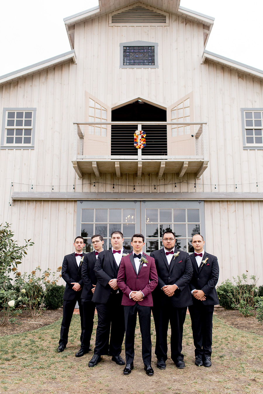 groom and his groomsmen in front of the barn