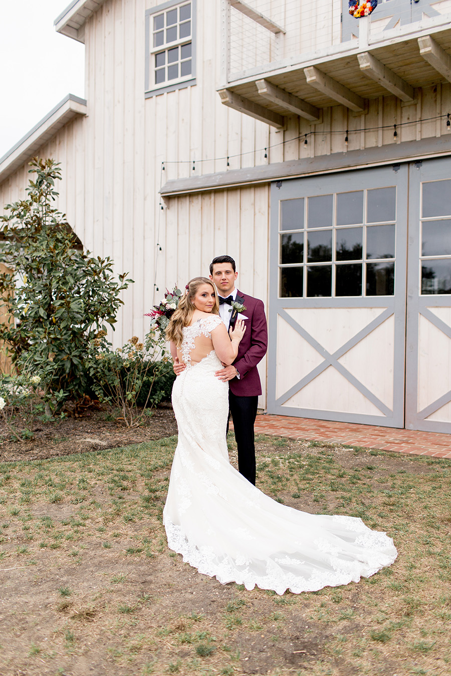 groom in a maroon tux and black bow tie