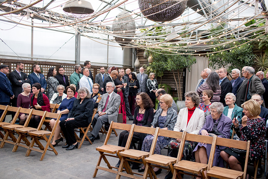 guests seated at indoor greenhouse ceremony space at terrain