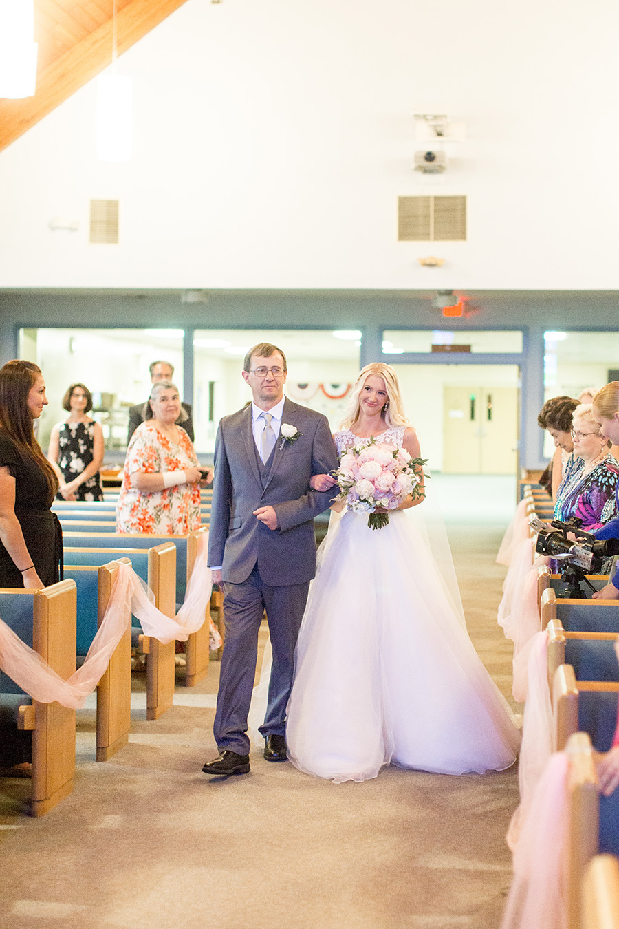 bride walks down church aisle