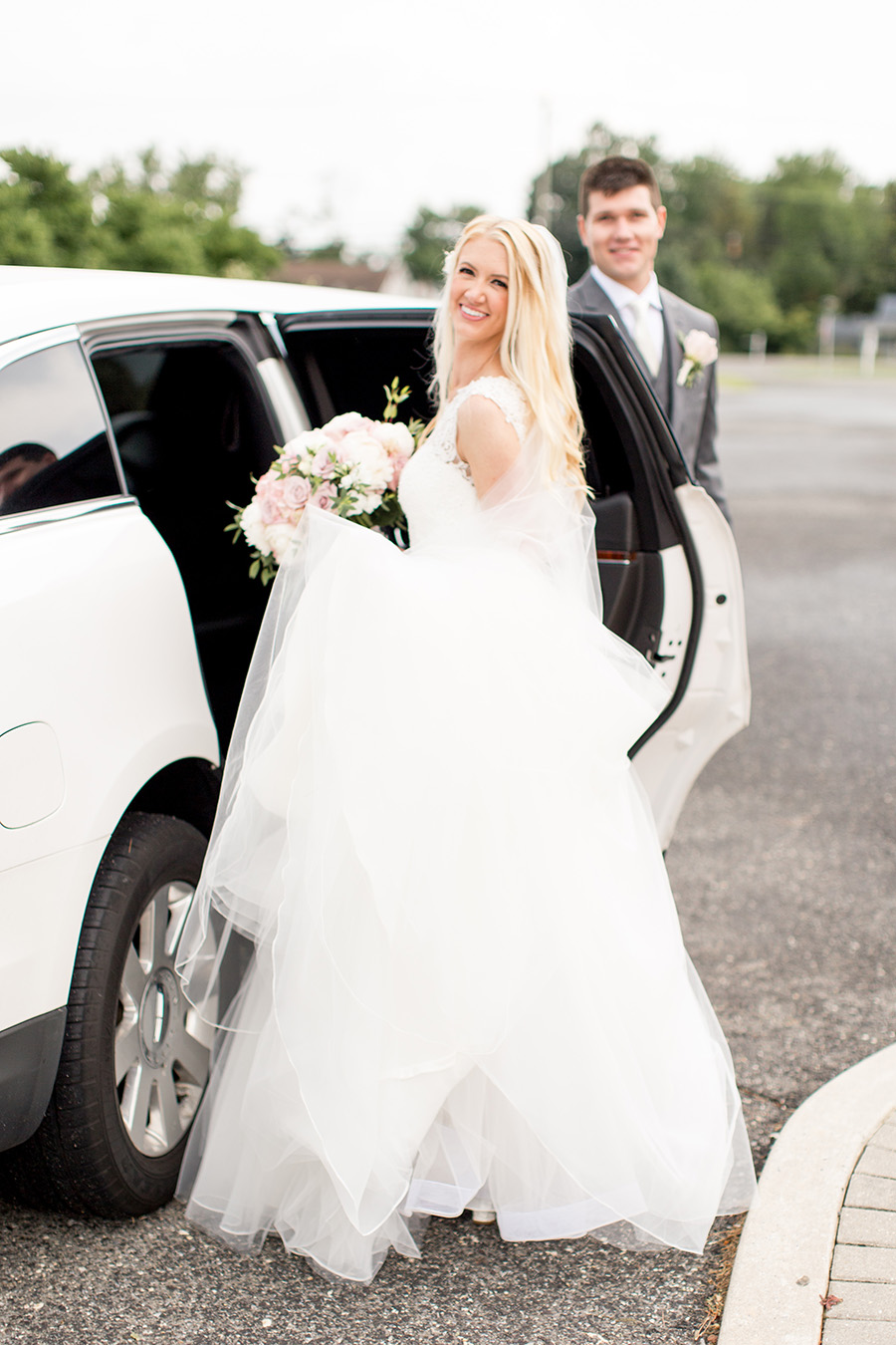bride and groom head to blue heron in a limo