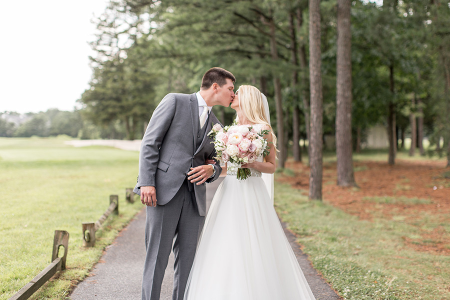 wedding couple share a kiss near blue heron golf course