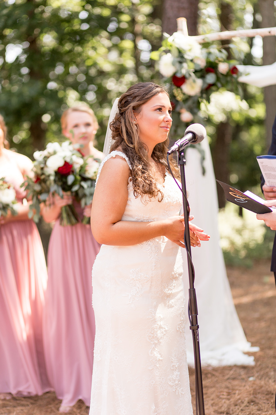 bride listens to her groom read his vows
