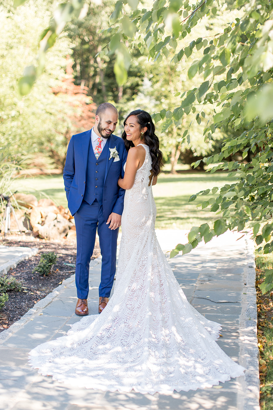 Bride's train spread out behind her as she poses with her groom