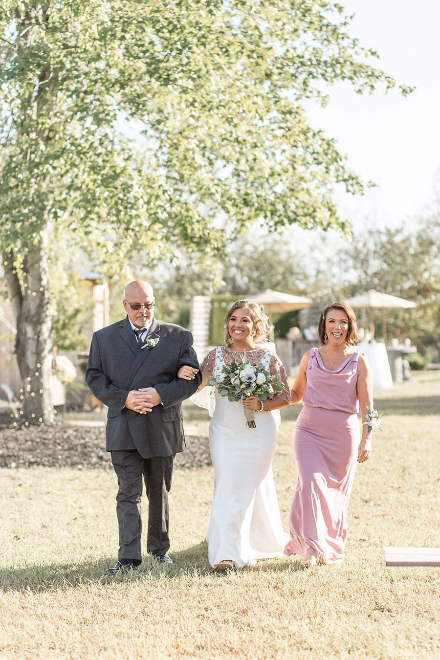 Brides walks down the aisle with her parents