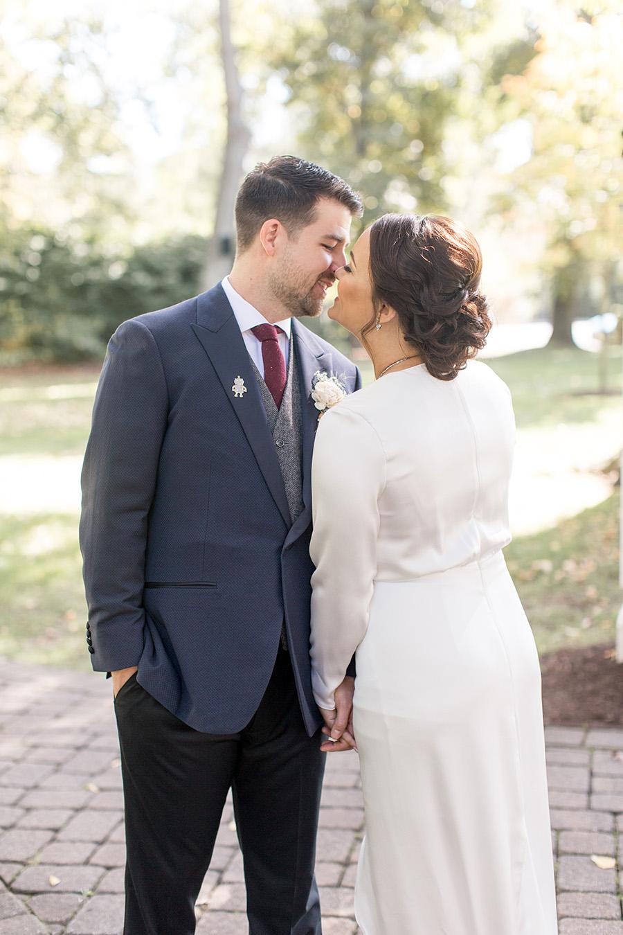 Groom in navy suit and bride in modern wedding dress