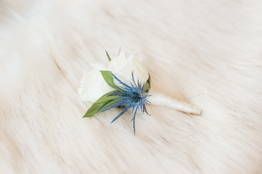 groom's wedding boutonniere with white roses and blue cornflower