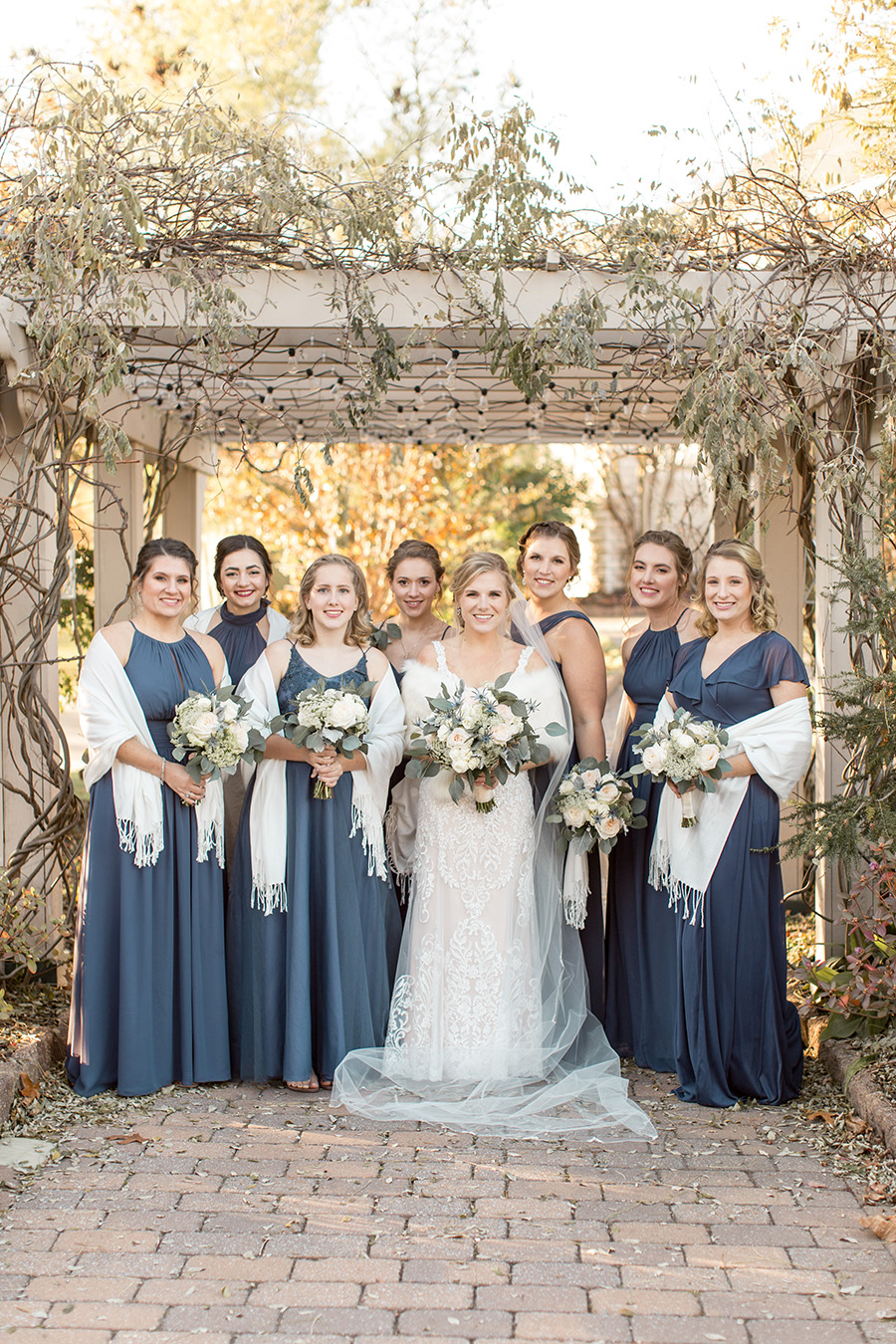 Bride and her bridesmaids in long winter blue dresses and shawls