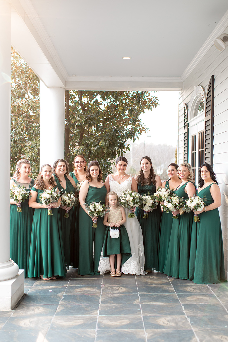 bride and her bridesmaids in emerald green full length gowns with white bouquets