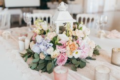 White Birdcage style wedding centre piece with beautiful pastels flowers and eucalyptus leaves