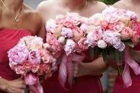 three brides maid bouquets in shades of red and pink