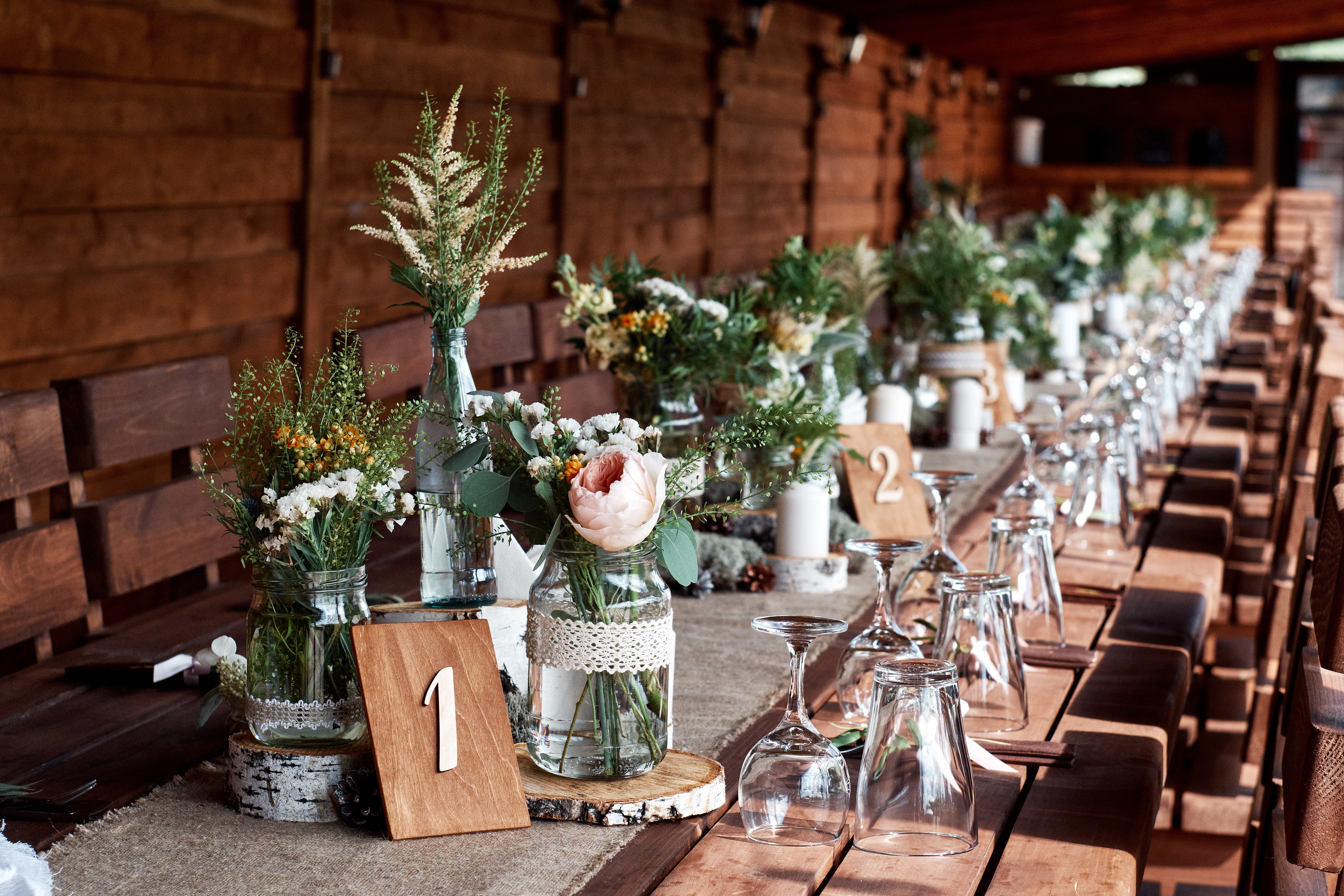 decorated wedding table with lots of small vases and containers of rustic garden flowers