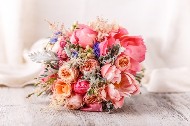 Bride's beautiful bouquet of roses on a white wooden background