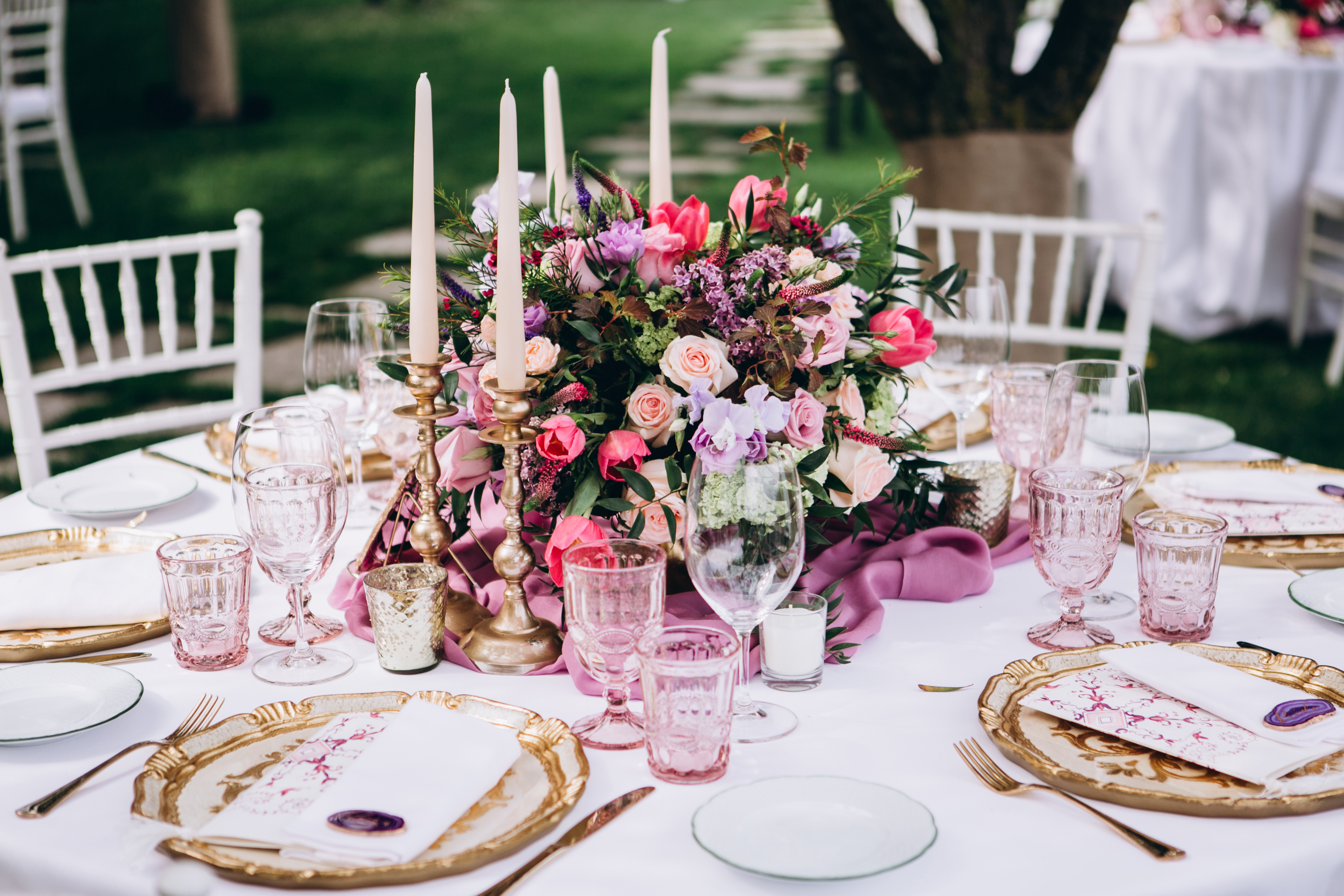 Table centrepiece floral decoration in pinks and purple on round wedding table including candles in brass holders and pink wine glasses