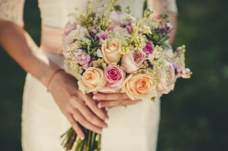 Bride carrying beautiful pastel bouquet, peach and pink with berries and foliage