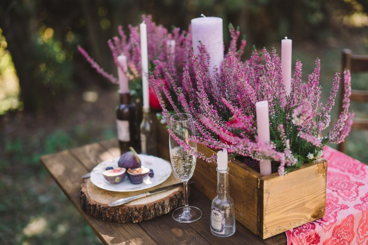 wooden brown flowerpot with heather on a decorated vintage table outdoors in the forest