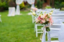 White chair standing on a green glade, prepared for the wedding ceremony. The chair is decorated with a bouquet of flowers. The background is blurred.