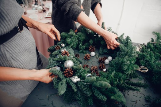 Christmas tree wreath decoration with woman hand workshop DIY.