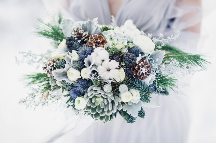 Winter wedding bouquet in hands of bride.