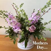 hat box of spring flowers in lilac and purple for mothers day