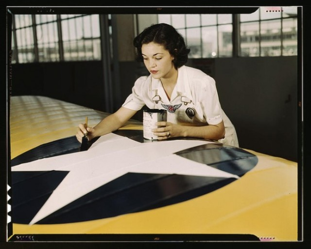 Mrs. Irma Lee McElroy painting the American insignia on airplane wings. Naval Air Base in Corpus Christi, Texas in August, 1942