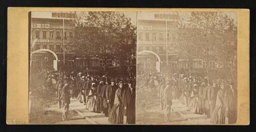Photograph shows a group of citizens entering the grounds of the Illinois state house to view the body of Abraham Lincoln on May 3 or 4, 1865. Two soldiers stand near the specially built arch. The African American man with the cane near the head of the line is Reverend Henry Brown.