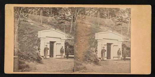 Photograph shows the public receiving tomb of Abraham Lincoln at Oak Ridge Cemetery. One man is seated in the foreground and another man stands at the entrance to the vault along with two soldiers in uniform.