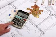 depositphotos_16512619-Hands-with-house-construction-plan-calculator-money-coins