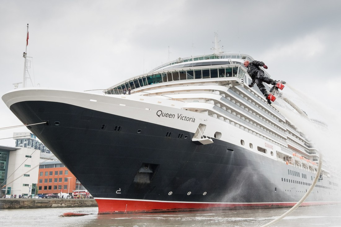 Cunard liner Queen Victoria arrives for the weekend in Liverpool, UK, 30th May, 2014. A man using a water based jet pack flies up to meet the captain of the Queen Victoria and welcome him to Liverpool.