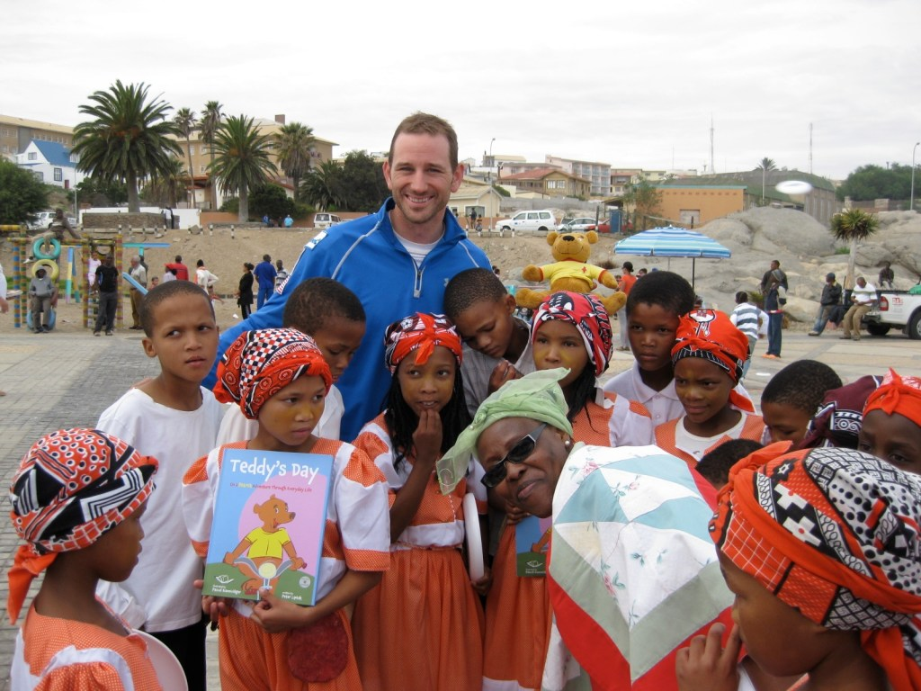 Peter Liptak posing with children of Namibia holding Teddy's Day