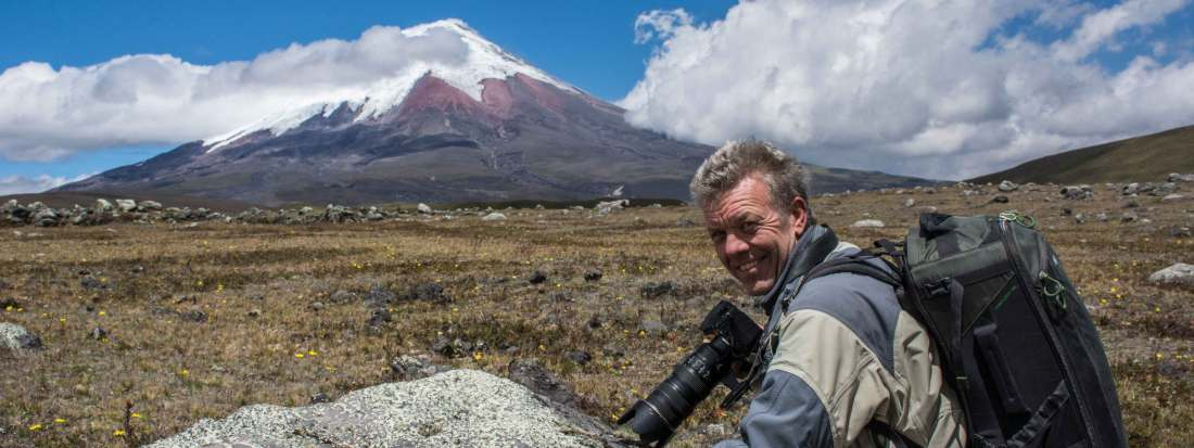 Conservation Photographer Pete Oxford sits in front of Cotopaxi Volcano in Ecuador.