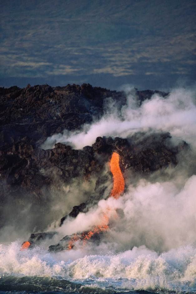 Hot lava flows into the ocean release large clouds of stream. Photo by conservation photographer and landscape photographer Pete Oxford.