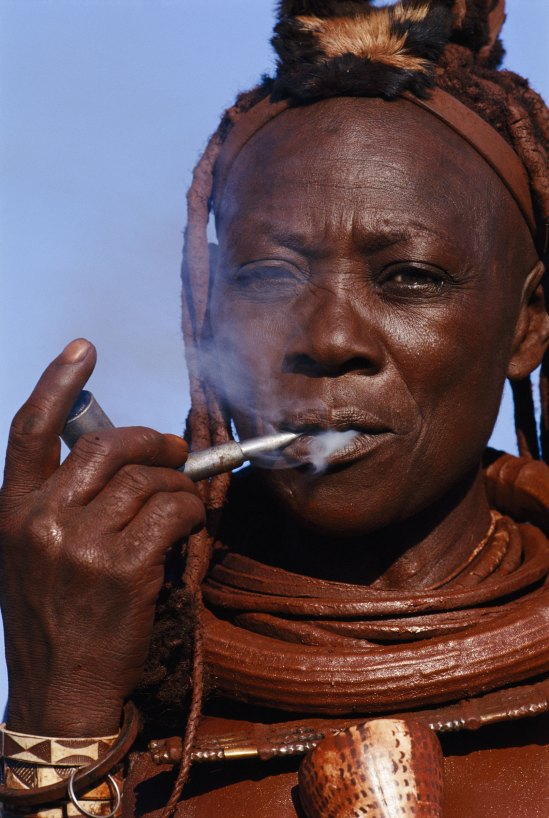 A Himba woman looks through the smoke coming out of her pipe at the camera. Photo by indigenous people photographer Pete Oxford.