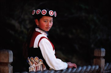 A Naxi girl poses for the camera in traditional dress. Photo by indigenous person photographer Pete Oxford.