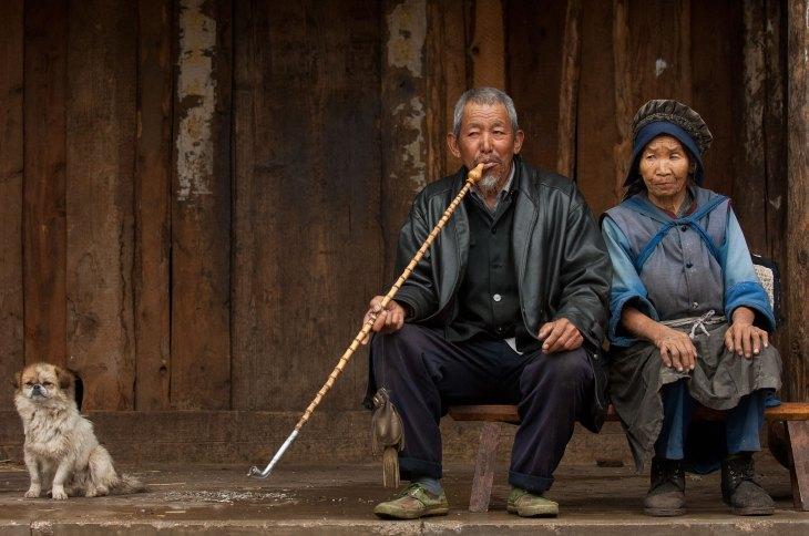A Naxi man smokes a long pipe with a woman sitting beside him. Photo by travel photographer Pete Oxford.